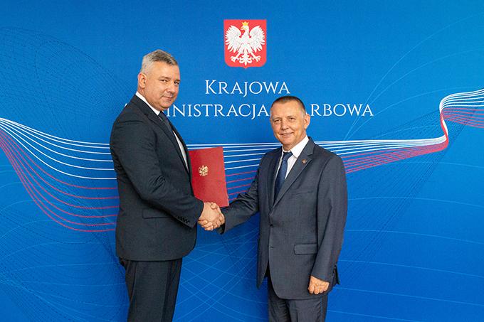 Uśmiechnięci minister finansów Marian Banaś i minister Piotr Dziedzic podają sobie ręce na tle banera Krajowej Administracji Skarbowej