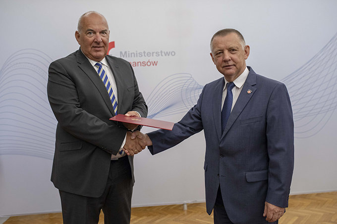 Minister finansów Marian Banaś i minister Tadeusz Kościński podają sobie ręce na tle baneru Ministerstwa Finansów