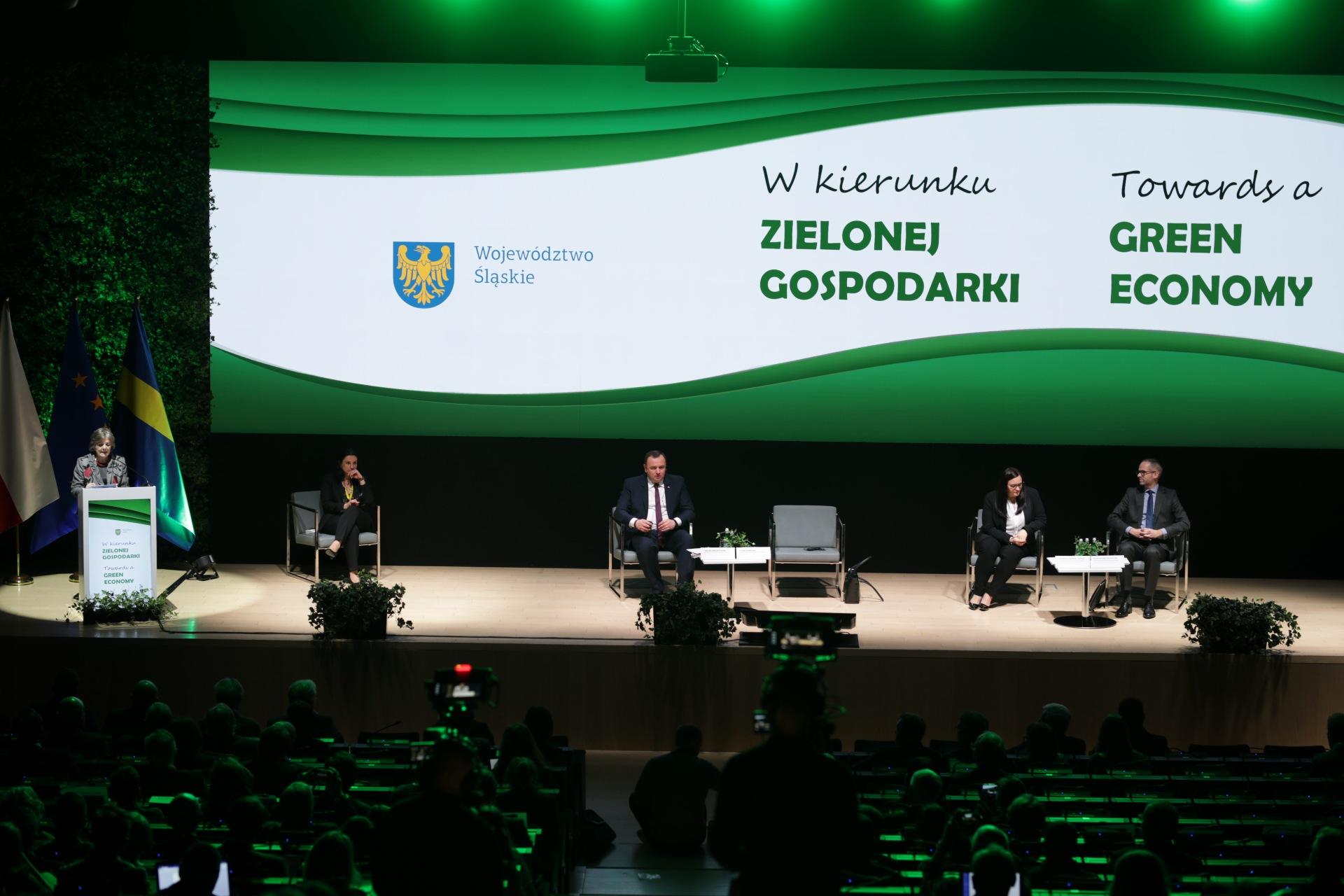 """Na scenie ustawione są fotele oraz mównica. Cztery osoby siedzą, piąta przemawia. Za nimi biało-zielony baner z napisami """"w kierunku zielonej gospodarki"""" oraz godło województwa śląskiego."""