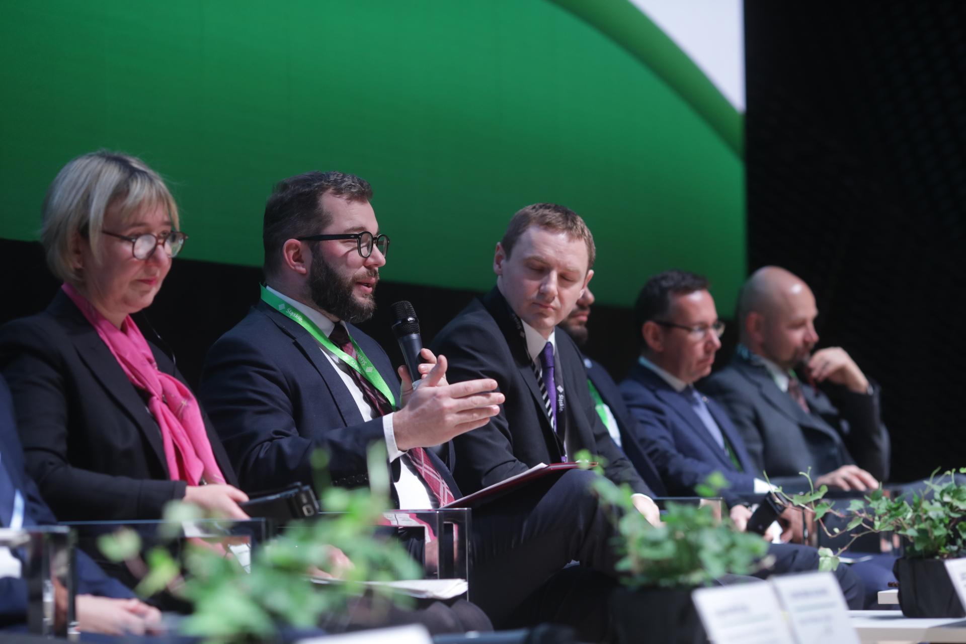 Na zdjęciu grupa ludzi siedząca w rzędzie. Drugi od lewej, wiceminister Grzegorz Puda mówi do mikrofonu.