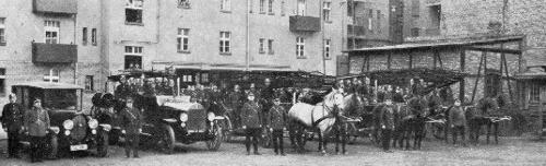 Wspólne zdjęcie na dziedzińcu strażnicy, na którym są wozy konne, samochody i strażacy zdjęcie czarnobiałe