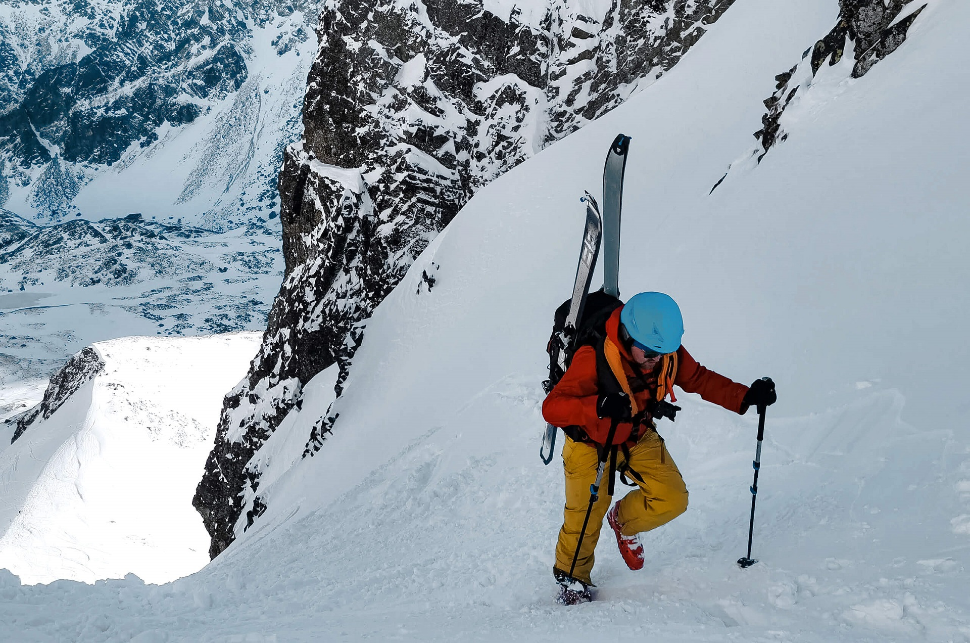 Man with skis climbing in the mountains, in winter, with the AEROSIZE avalanche vest