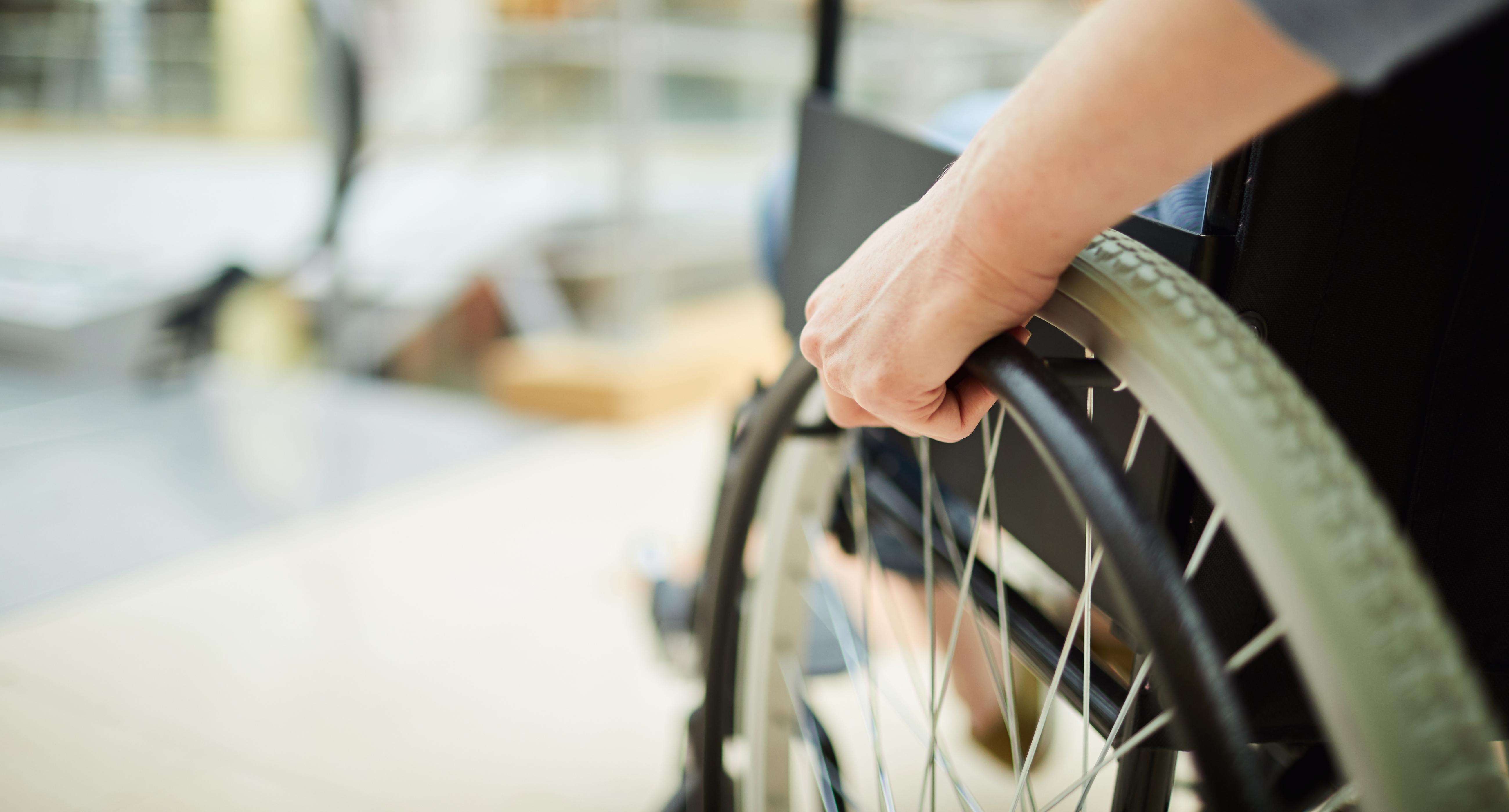 Lewa ręka trzyma koło wózka inwalidzkiego