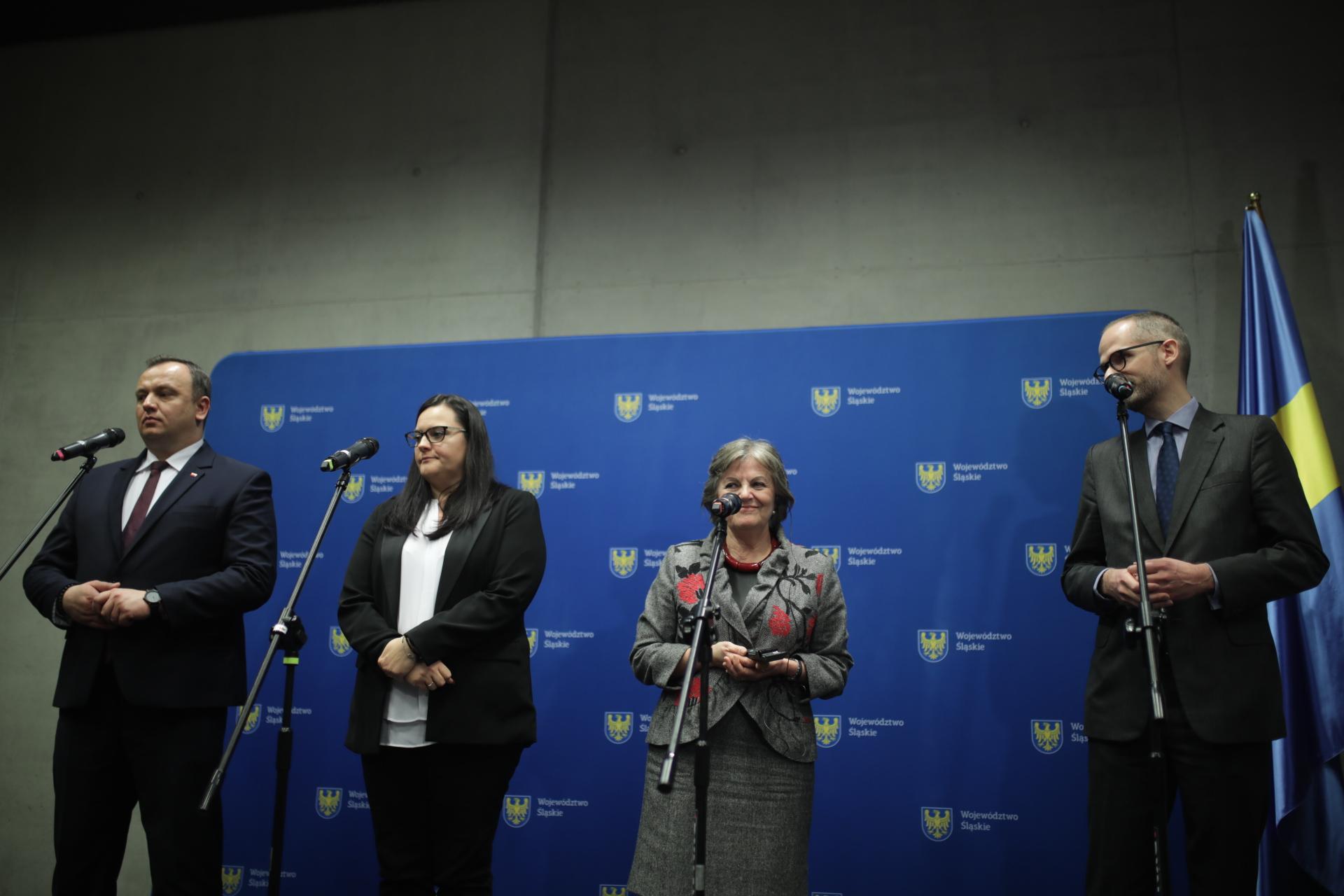 Na tle niebieskiej ścianki stoją przed mikrofonami dwie kobiety i dwóch mężczyzn.