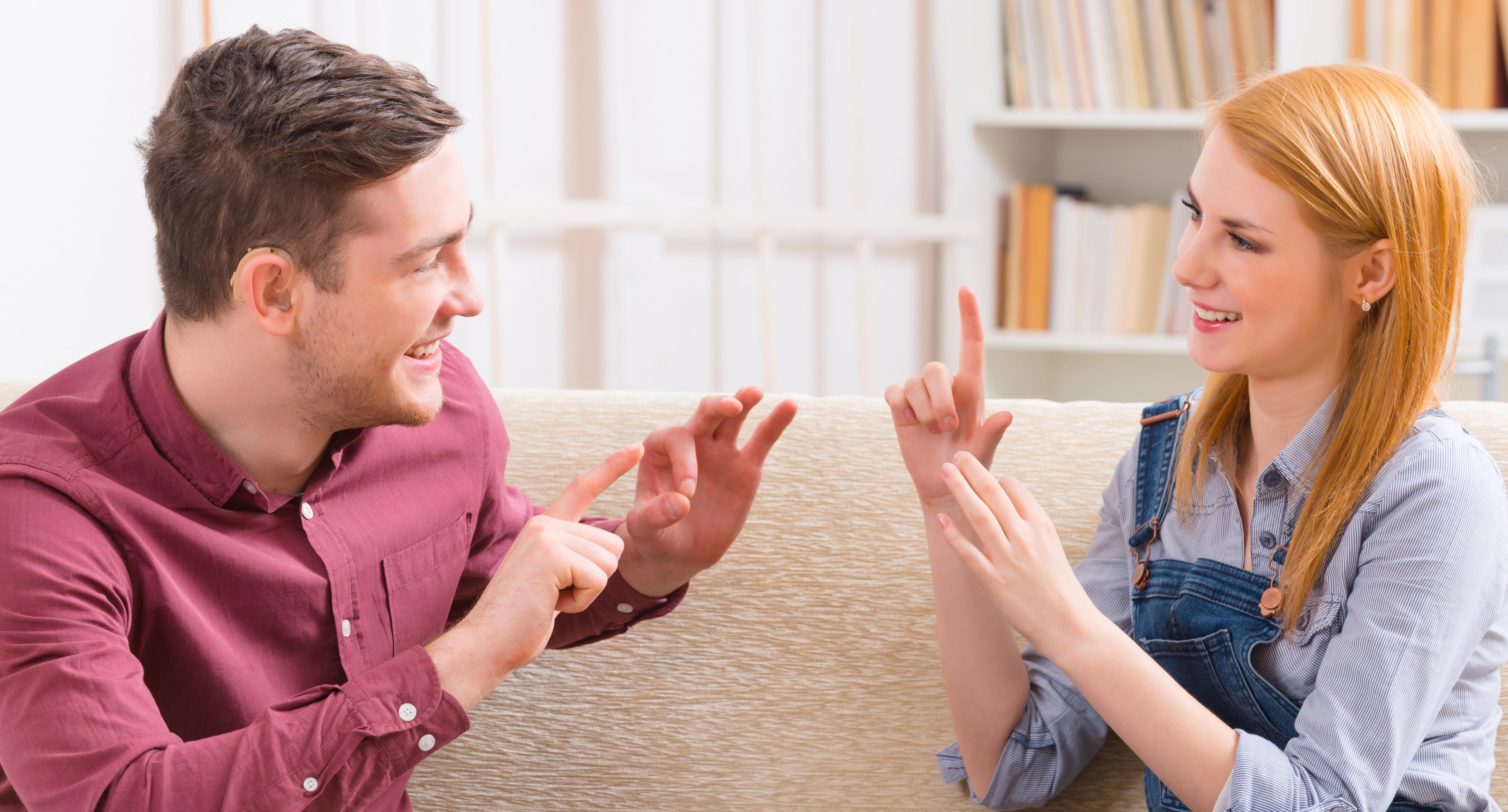Uśmiechnięty mężczyzna i kobieta komunikują się ze sobą językiem migowym