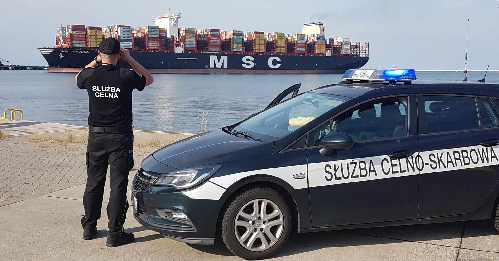 Funkcjonariusz Służby Celno-Skarbowej stojąc przy samochodzie obserwuje przez lornetkę kontenerowiec