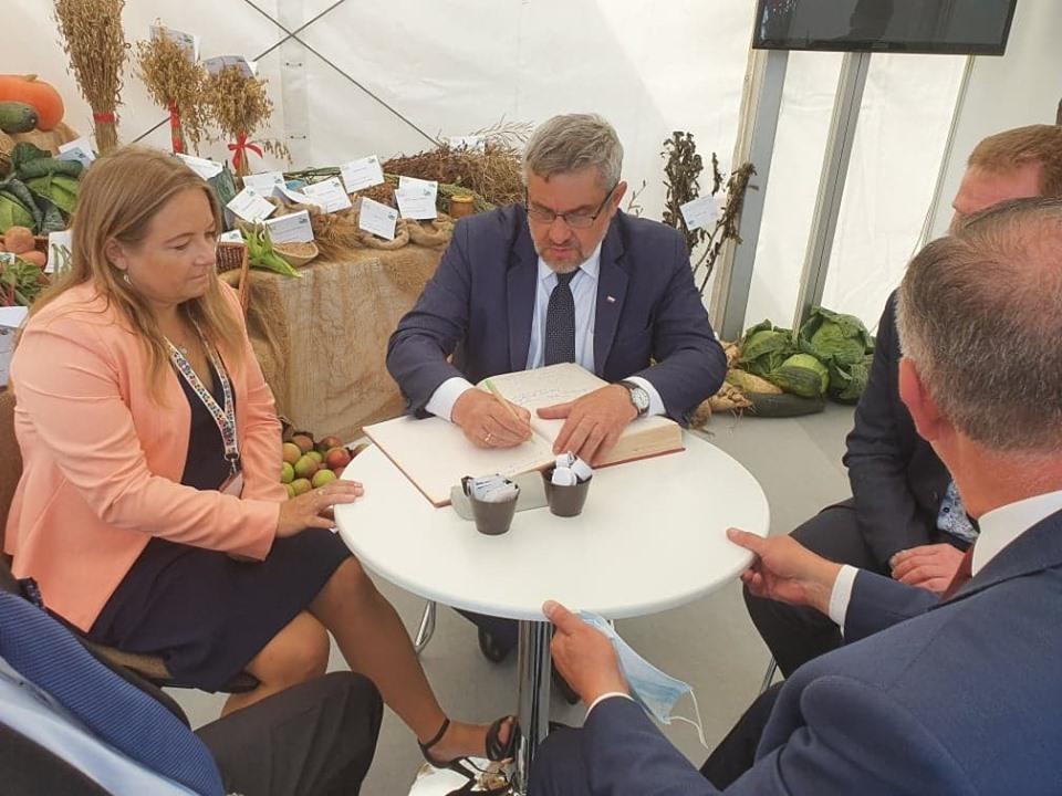 Minister J.K. Ardanowski wpisuje się do księgi pamiątkowej
