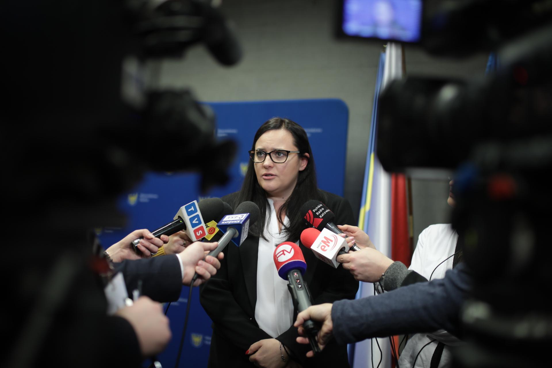 Na pierwszym planie Małgorzata Jarosińska-Jedynak. Wokół niej dziennikarze z mikrofonami i kamerami.