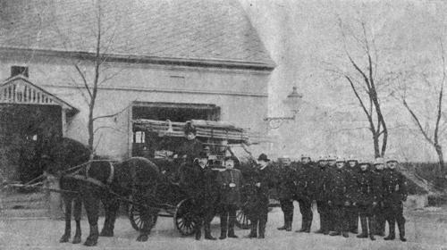 Wóz zaprzęgnięty w 2 konie i pozujący strażacy przed budynkiem zdjęcie czarnobiałe