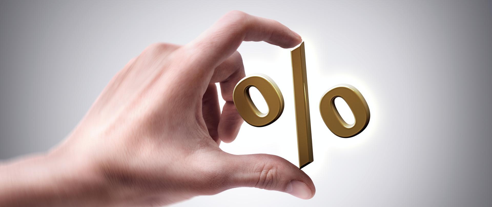 Złoty procent pomiędzy dwoma palcami
