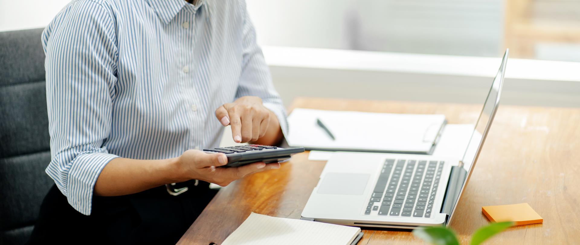 Kobieta wykonuje działania matematyczne na kalkulatorze parząc się przy tym jednocześnie na laptopa.