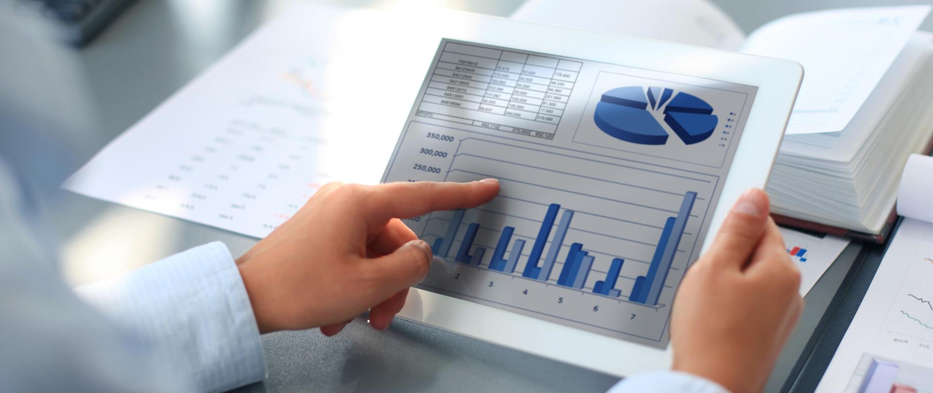 Tablet na którym widać wykresy kołowe, słupkowe i dane tabelaryczne