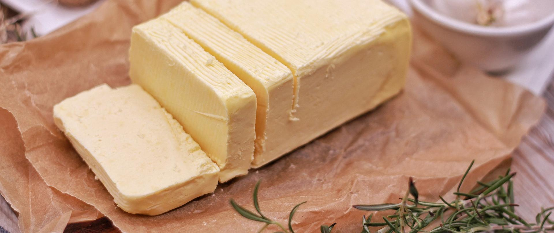Na środku na papierze do pieczenia znajduje się margaryna w kostce, obok leży gałązka rozmarynu, w tle miska z główką czosnku.
