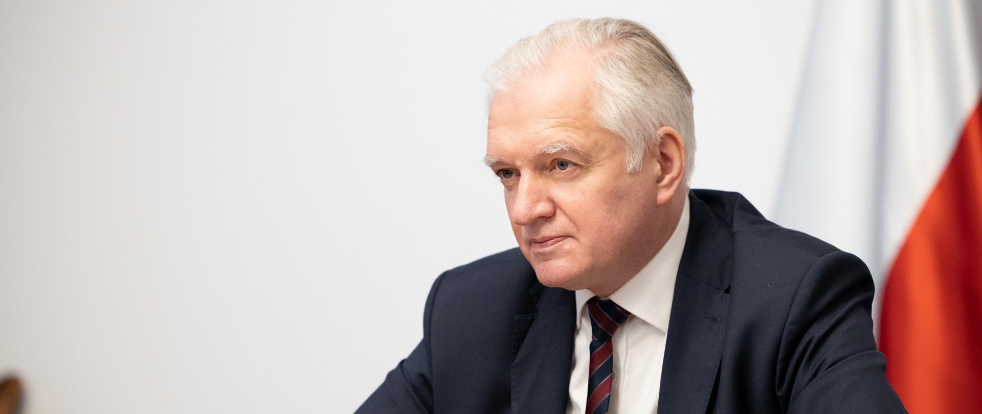 Sektor spożywczy i drobny handel skorzysta na tarczy branżowej- Jarosław Gowin przy stole konferencyjnym, za nim flagi, przed nim mikrofon. Widok z boku.