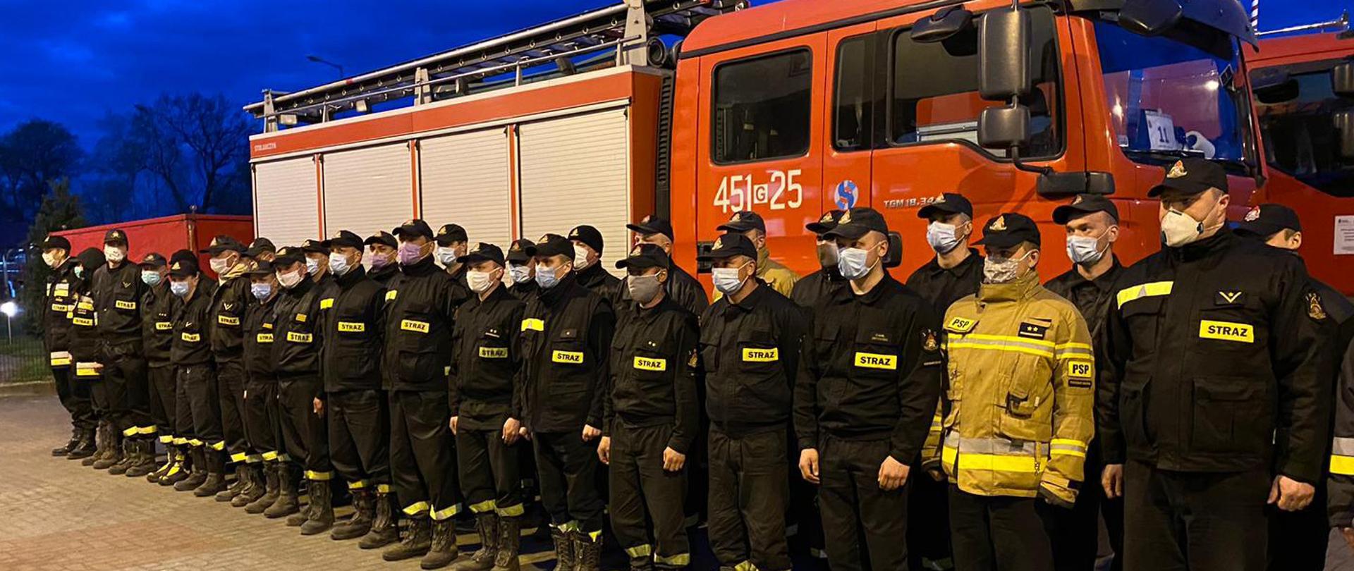 Strażacy z maseczkami zakrywającymi nos i twarz, stojący w dwuszeregu, na tle ciężkiego samochodu gaśniczego.
