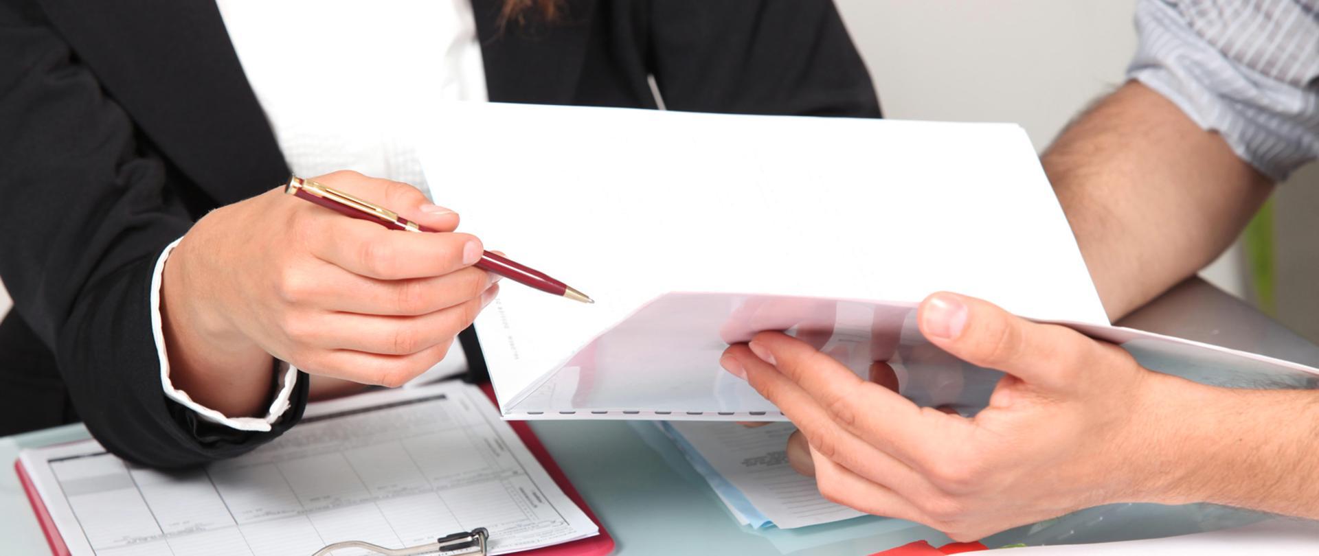 Dłonie dwóch osób, jedna długopisem wskazuje na dokument.