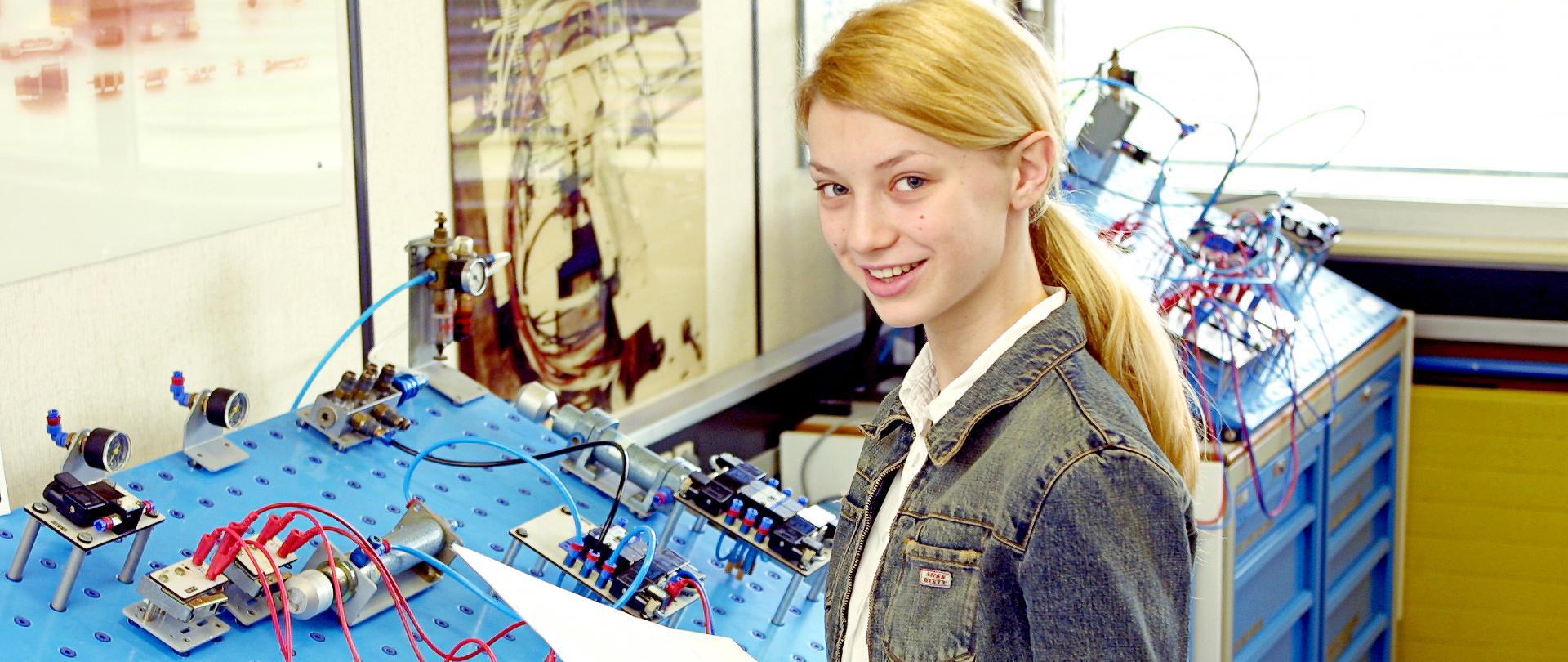 Młoda dziewczyna łączy obwód elektryczny na płycie prototypowej.