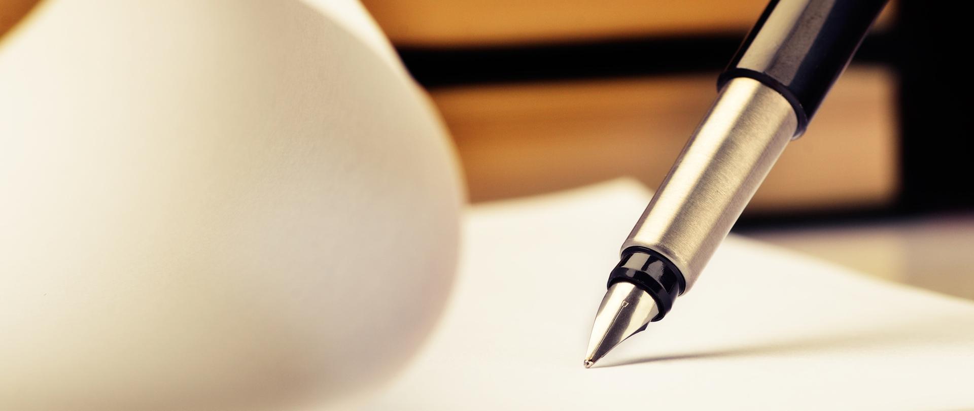 Pióro dotyka kartki papieru.
