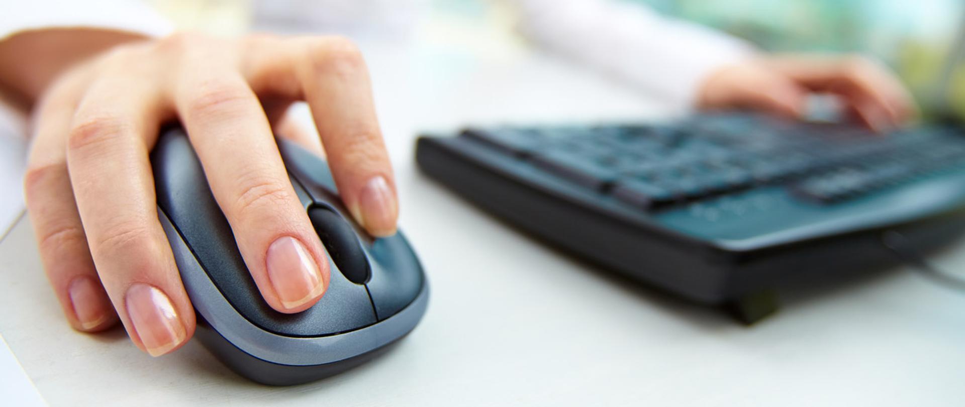 Dłoń na myszy komputerowe, druga na klawiaturze komputerowej.