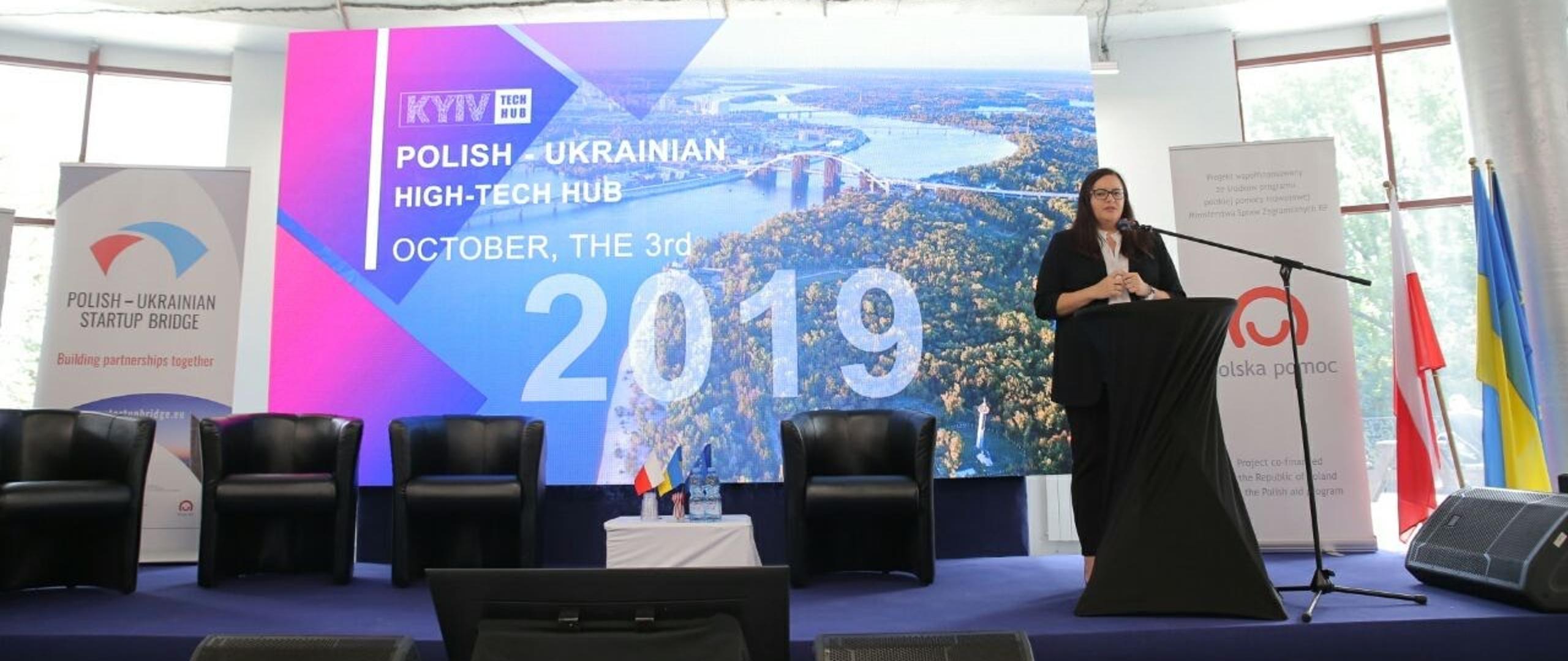 Wiceminister Małgorzata Jarosińska-Jedynak podczas otwarcia konferencji na scenie przy czarnej mównicy, z tyłu ekran z grafiką promocyjną wydarzenia z napisem: