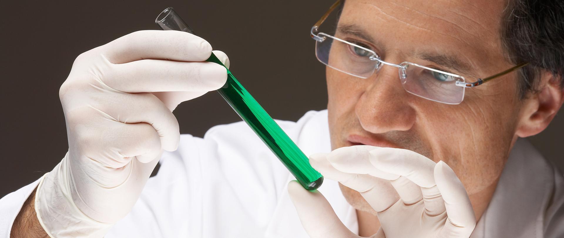 Naukowiec w białym fartuchu ogląda zawartość probówki.