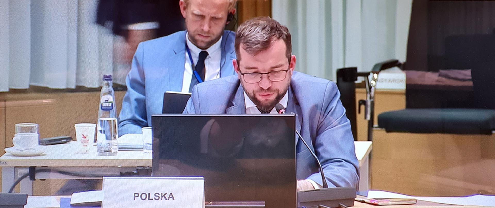 Minister Grzegorz Puda siedzący przy laptopie podczas obrad