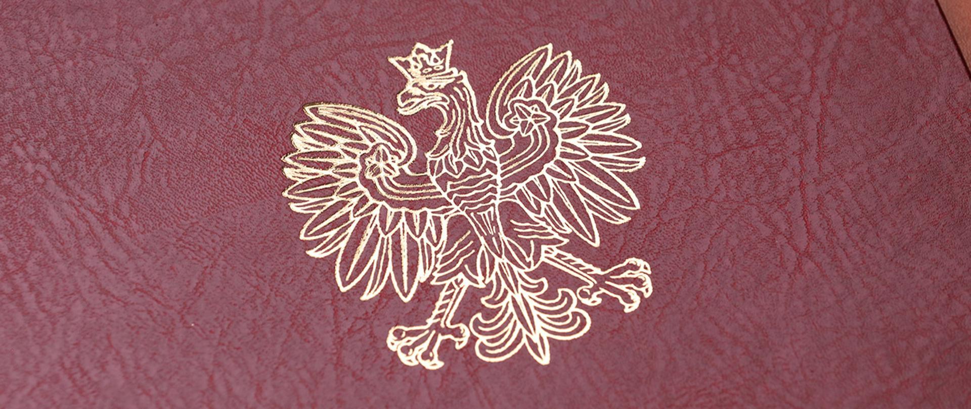 Na zdjęciu widać fragment twardej oprawy na dokumenty z wytłoczonym orłem z godła narodowego.