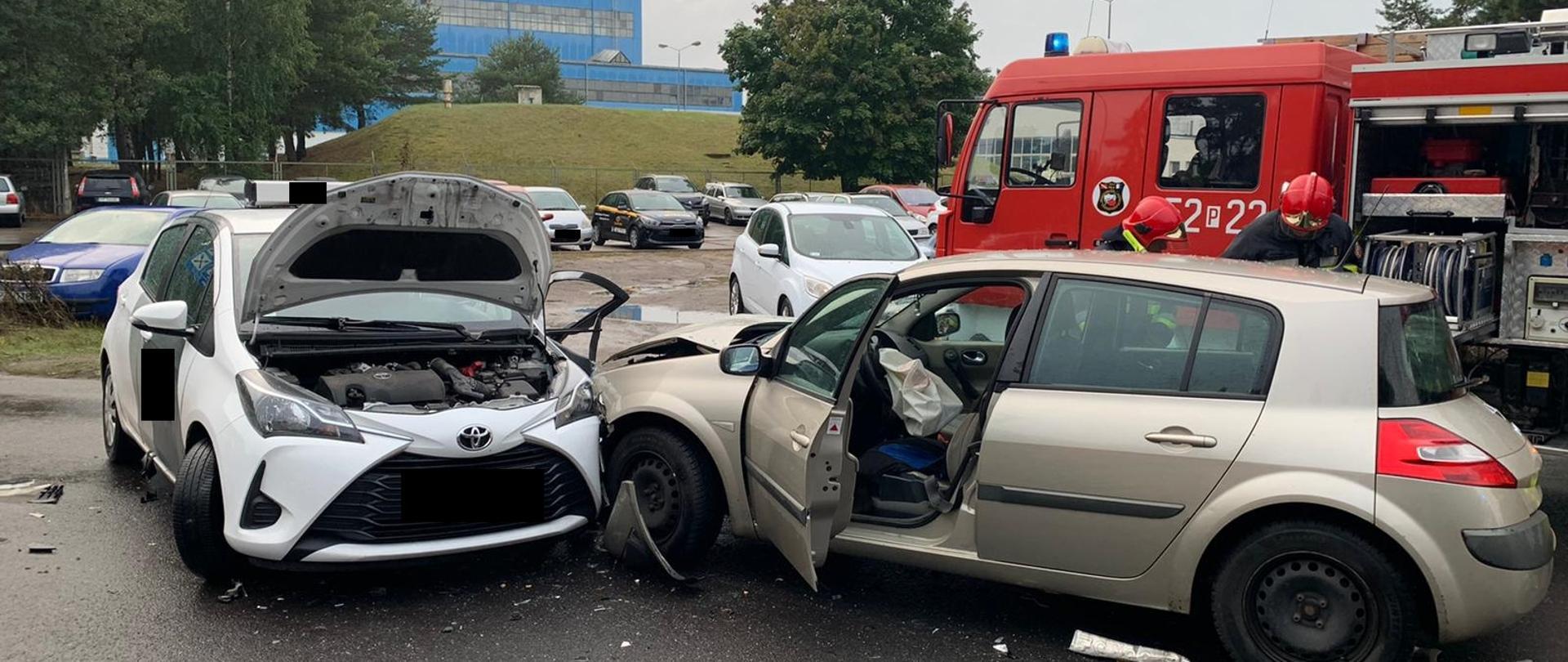 Na zdjęciu widać dwa uszkodzone samochody po zdarzeniu oraz pojazd straży pożarnej w tle.