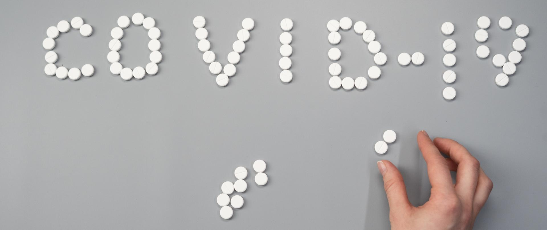 Napis Covid-19 ułożony z tabletek, fot.: cottonbro