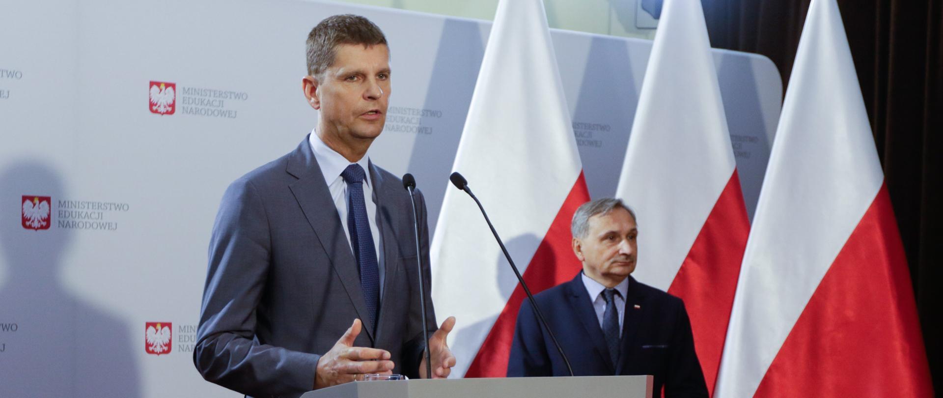 Minister Edukacji Narodowej Dariusz Piontkowski i wiceminister Maciej Kopeć podczas konferencji. W tle biała ścianka z logo ministerstwa oraz flagi Polski.