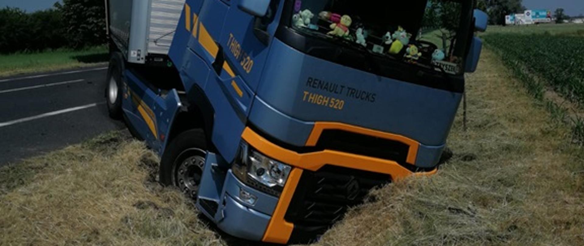 Samochód ciężarowy wbity przodem w ziemie rowu. Przyczepa stoi na drodze.