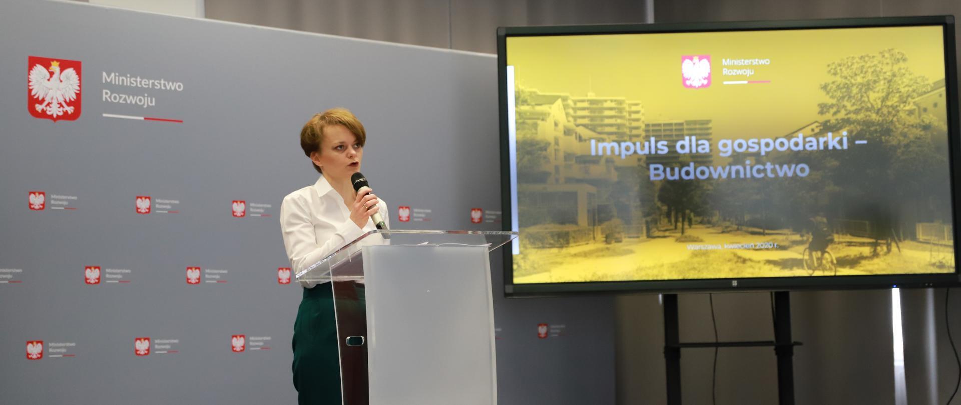 Wicepremier Jadwiga Emilewicz w trakcie przemówienia. Stoi za mównicą, na tle ścianki z logo MR, po prawej stronie ekran, na którym wyświetla się hasło Impuls dla gospodarki - Budownictwo.