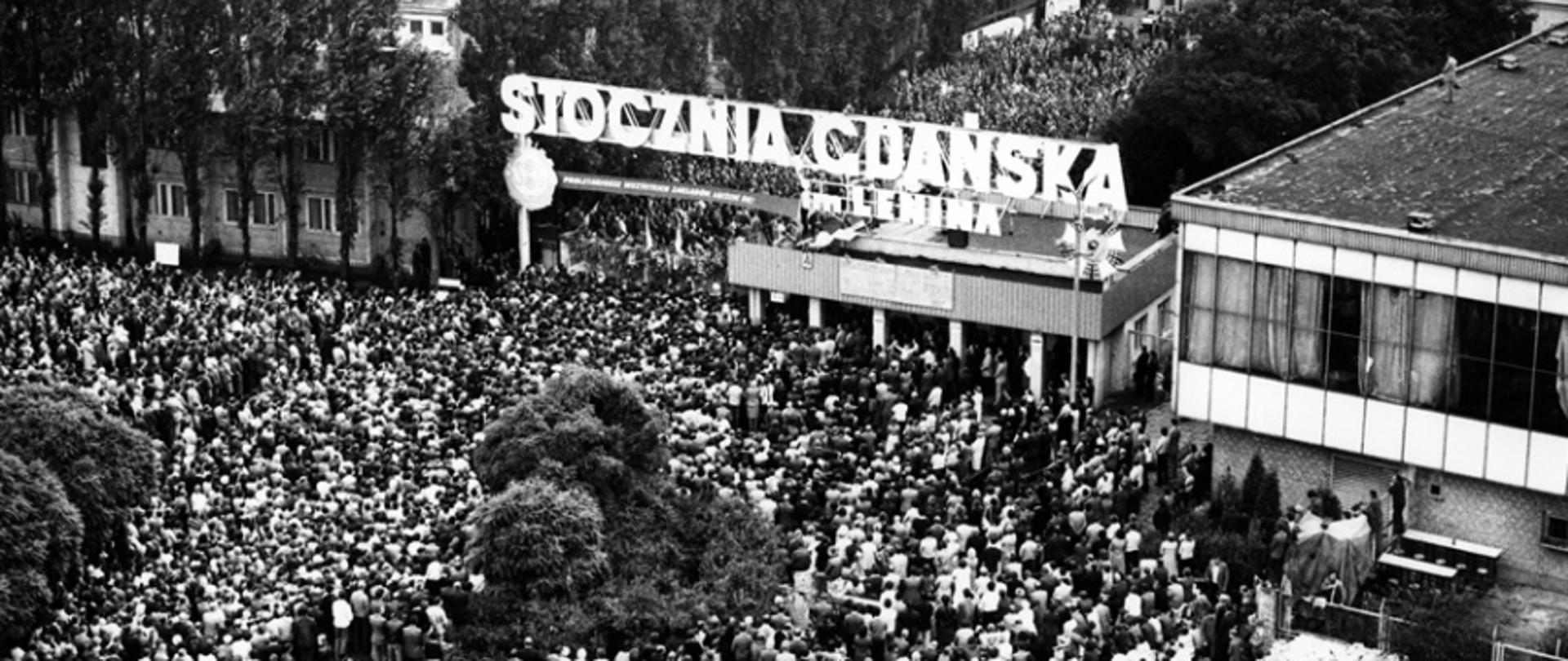 "August strike at Lenin's Shipyard in Gdansk. Top view of Gate No. 2 and the citizens and shipyard workers gathered below it. Above the gate, there is a banner with the slogan ""PROLETARIANS OF ALL FACTORIES UNITE!"", and on the roof of the guardhouse there are boards with 21 demands of MKS."