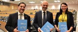 Wiceminister Michał Kurtyka na szczycie klimatycznym w Nowym Jorku pokazuje teczkę o elektromobilności