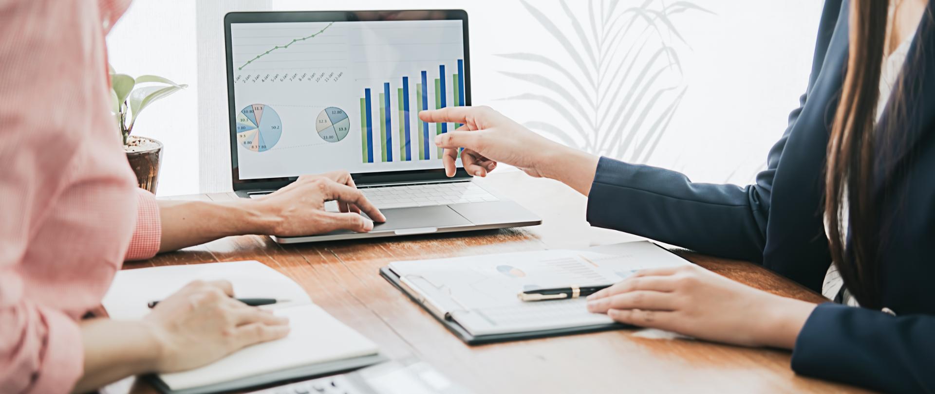 Dwie osoby rozmawiają na temat księgowania środków finansowych, w tym jedna wskazuje na ekran laptopa gdzie widoczny jest wykres
