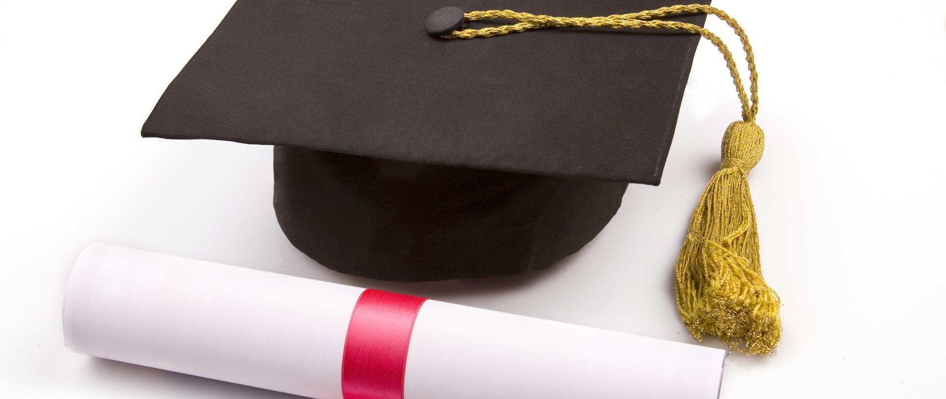 Na zdjęciu widać biret studenta i zwinięty w rulon dyplom.