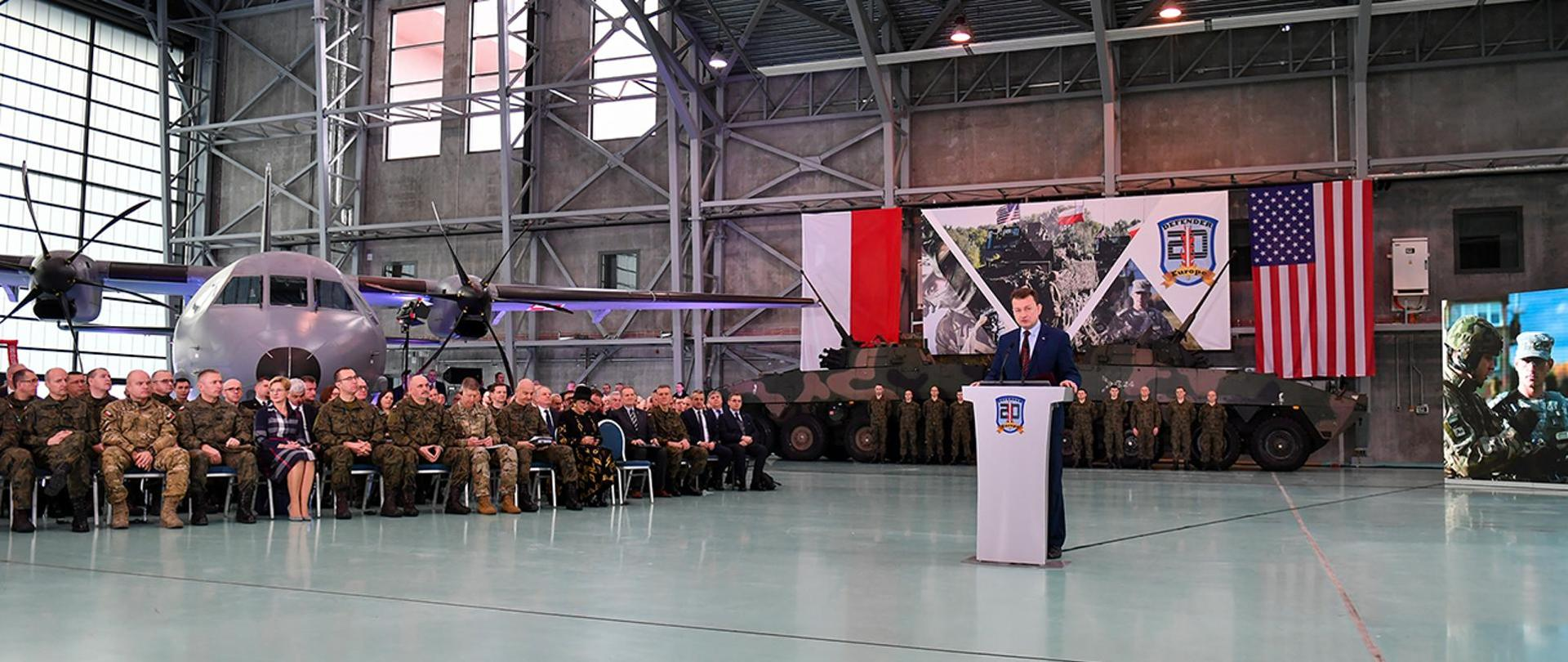 Defence Minister Mariusz Błaszczak gives a speech. Briefing on the Defender Europe 20 exercise, soldiers and armored vehicles in the background. PL and USA flags.
