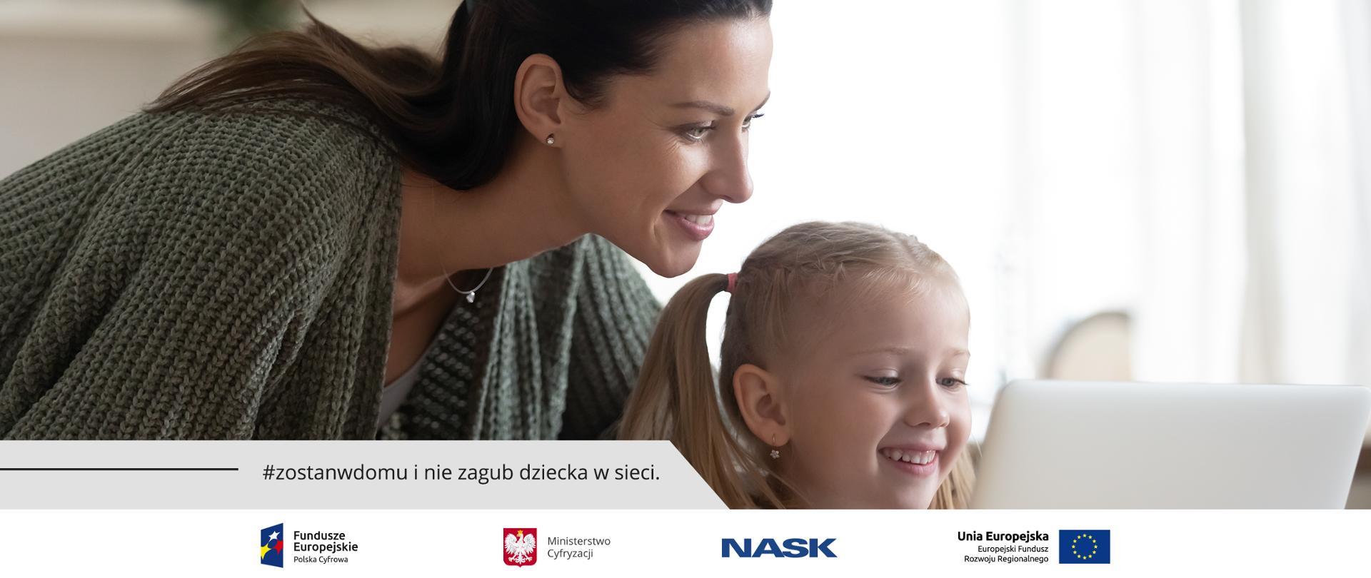 Uśmiechnięta dziewczynka siedzi przed laptopem. Za nią stoi jej mama i tez patrzy w monitor