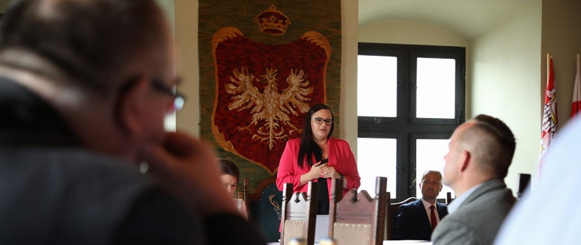 Minister Małgorzata Jarosińska-Jedynak przemawia na spotkaniu z samorządowcami i przedsiębiorcami w sali urzędu