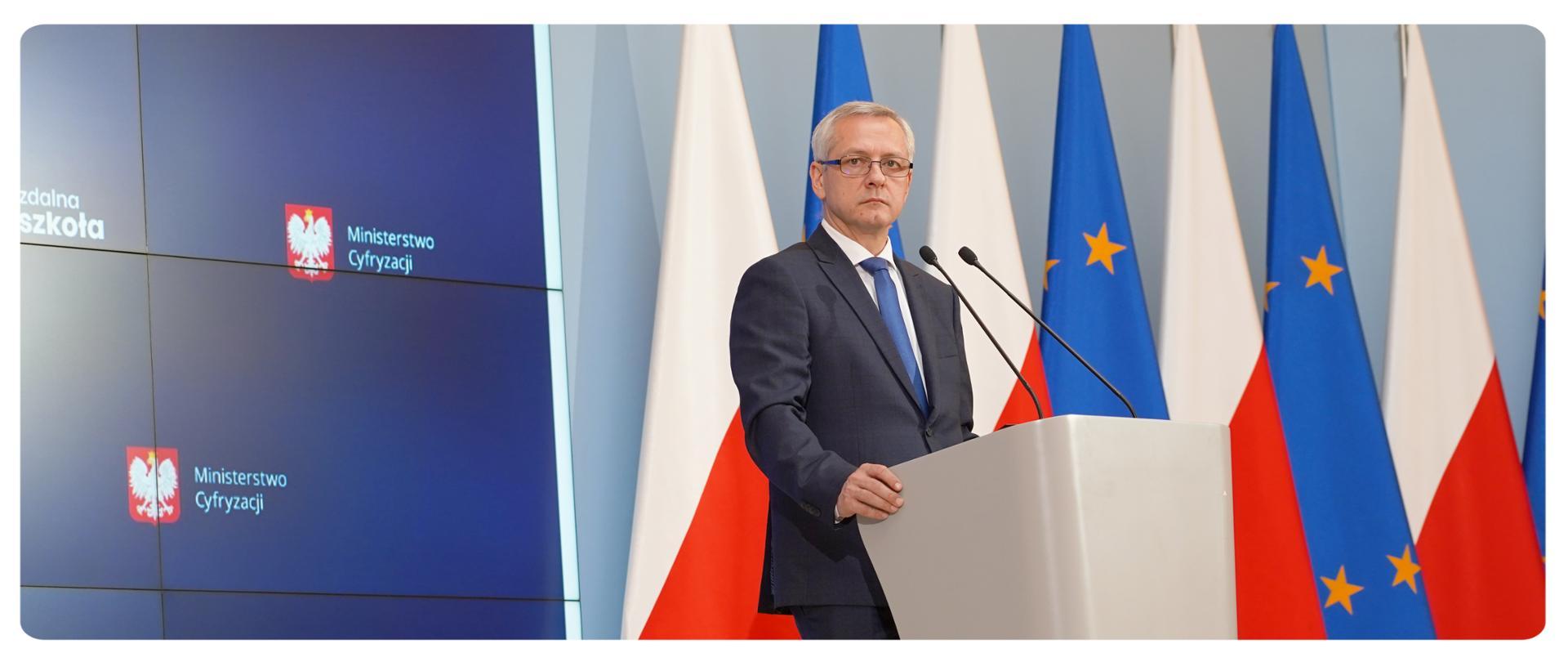 Minister Marek Zagórski przy mównicy, patrzy w prawą stronę. Za nim na ekranie fragment prezentacji - widać dwa logotypy MC na granatowym tle. Po lewej stronie ministra flagi: polskie i unijne