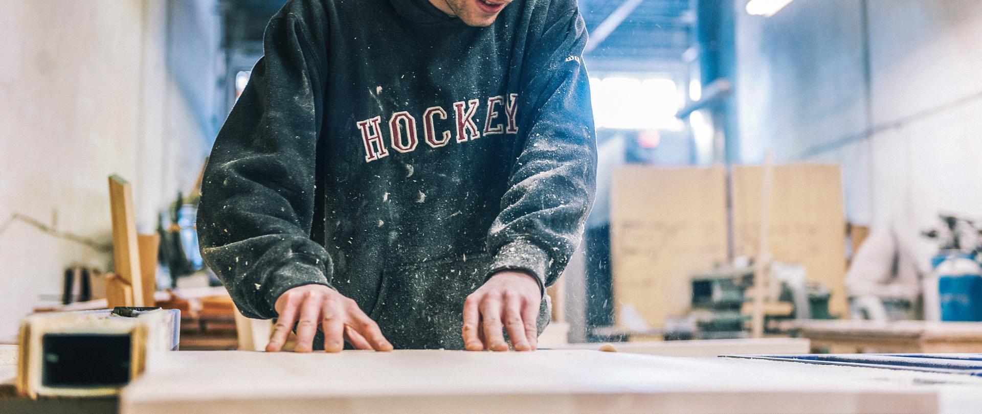 Pracownik stolarni - młody mężczyzna przy obróbce drewna