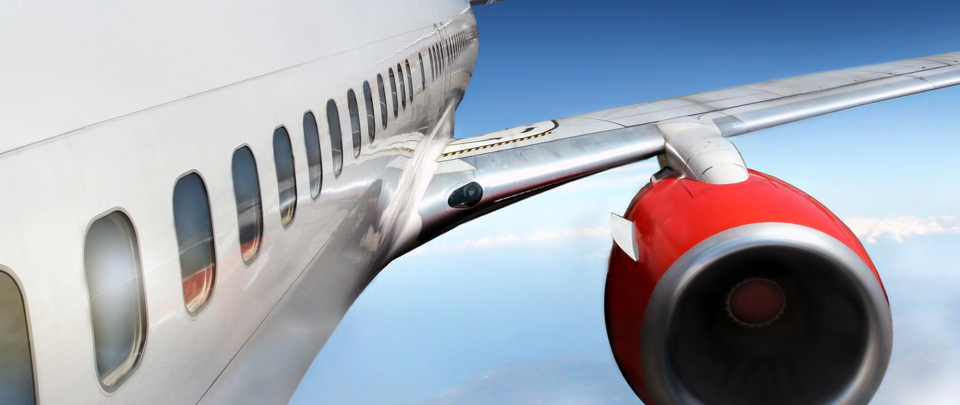 Skrzydło samolotu z silnikiem, w tle chmury