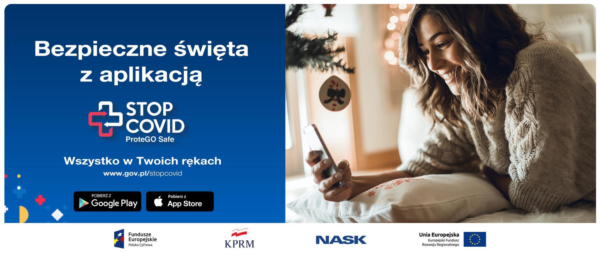 Ekran podzielony na pół. Z prawem strony kobieta obok bożonarodzeniowej choinki - opiera się o poduszkę, patrzy na trzymany w dłoni telefon. Z lewej strony, na granatowym tle tekst: Bezpieczne święta z aplikacją STOP COVID ProteGo Safe. Wszystko w Twoich rękach. www.gov.pl/stopcovid