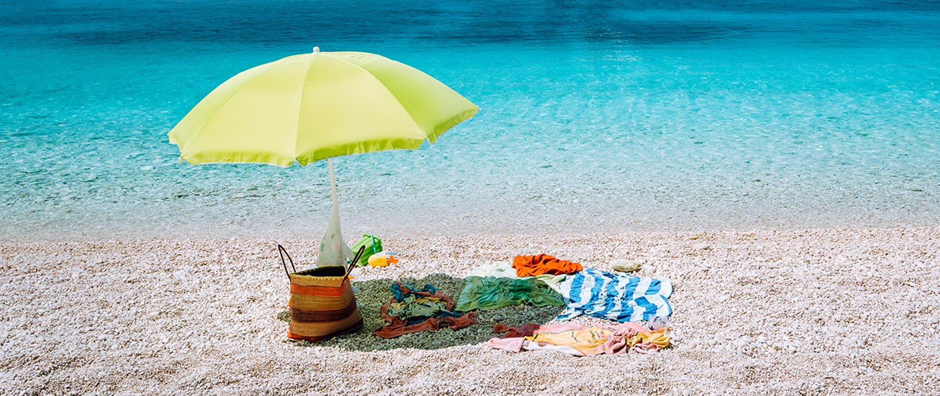 Plaża, nad wodą rozbity parasol.
