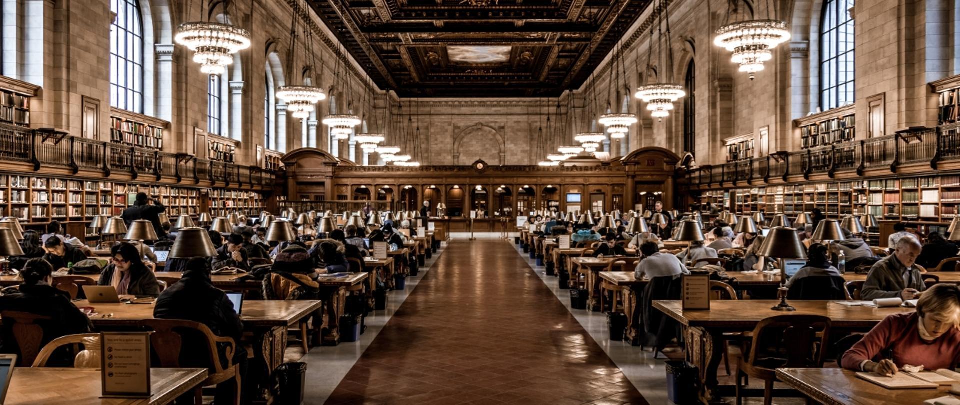Aula biblioteczna, wielu studentów czyta książki
