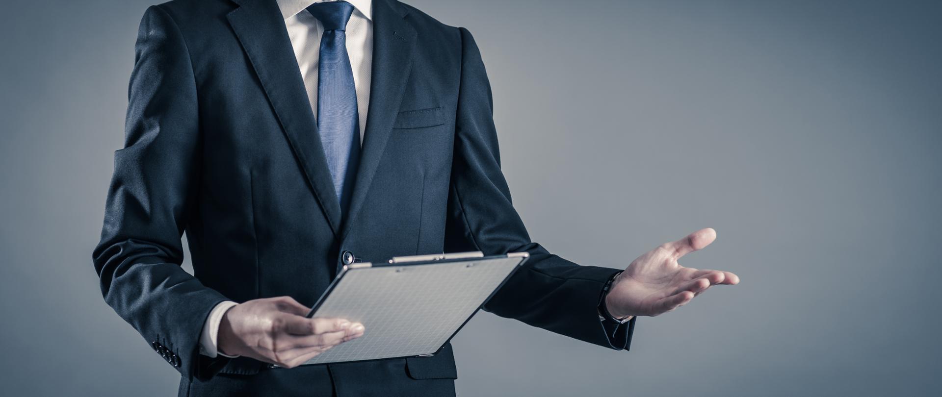 Elegancki mężczyzna w garniturze trzyma w prawym ręku deskę z klipsem