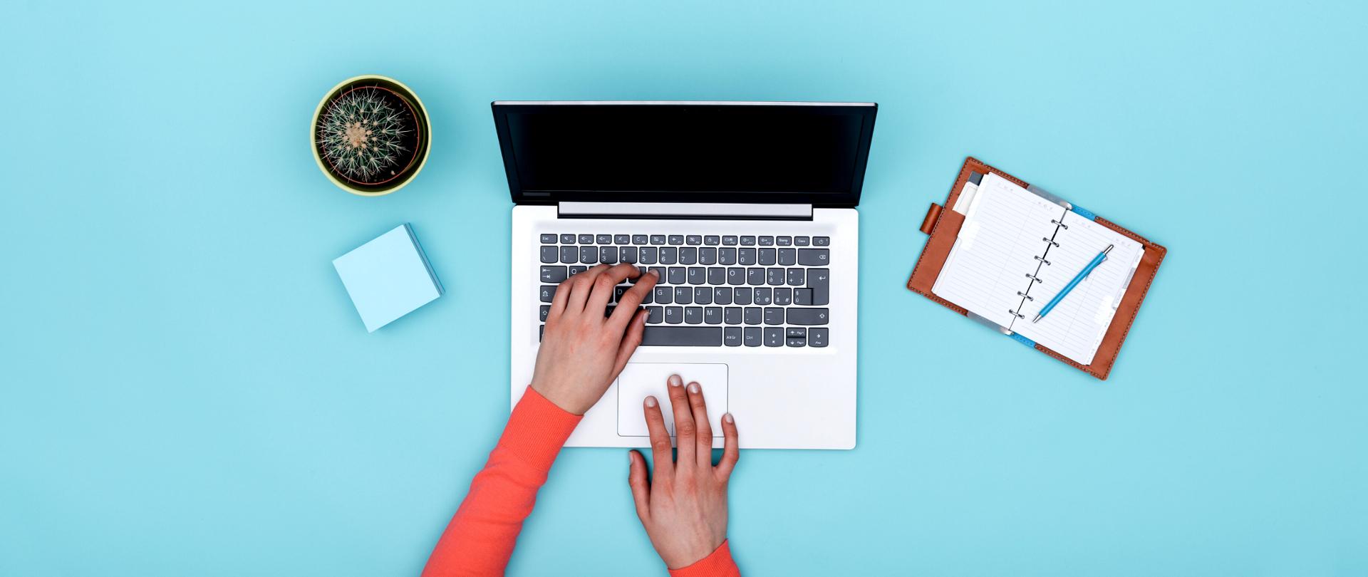 Dłonie pracujące na otwartym laptopie. Obok laptopa leżą notes i kaktus.