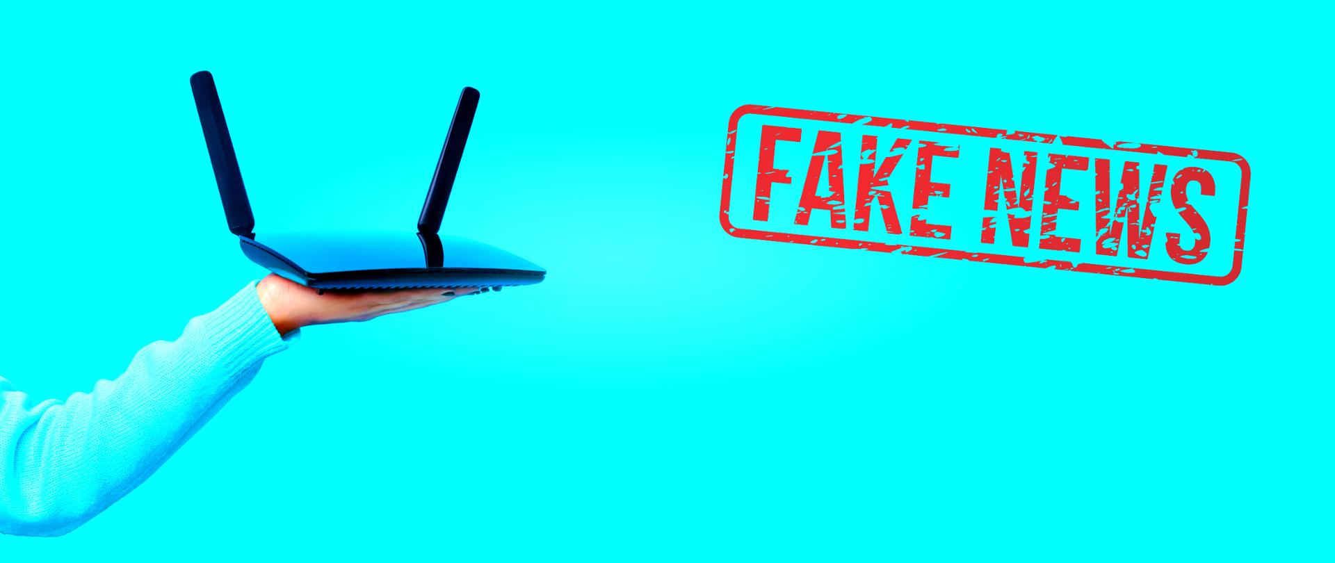 """Błękitne tło. Z lewej strony - wyciągnięta ręka z trzymanym na dłoni routerem. Z prawej czerwona pieczątka """"Fake news""""."""