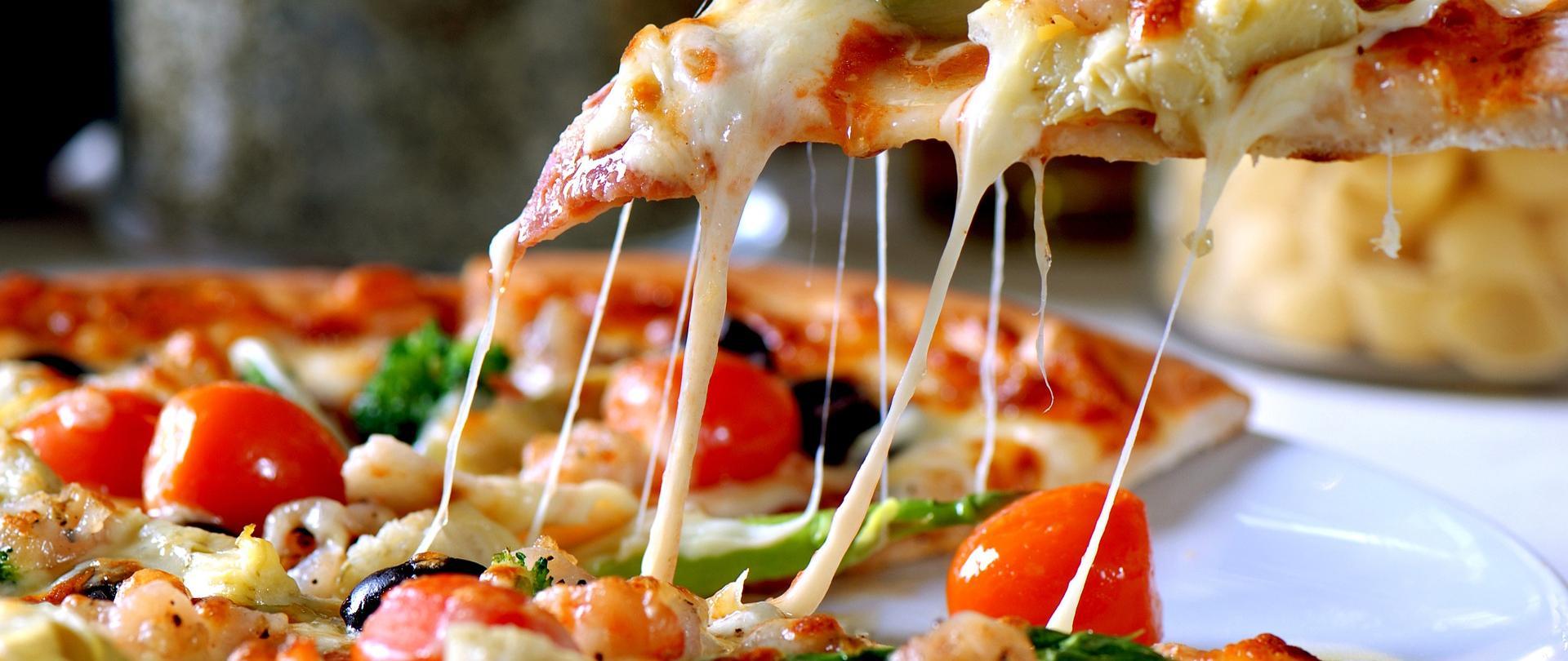 Na zdjęciu znajduje się pizza na talerzu - jeden kawałek z ciągnący żółtym serem jest odkrojony i podniesiony do góry. Na pizzy są: koktajlowe pomidorki, czarne oliwki, krewetki, brokuł, ser żółty.