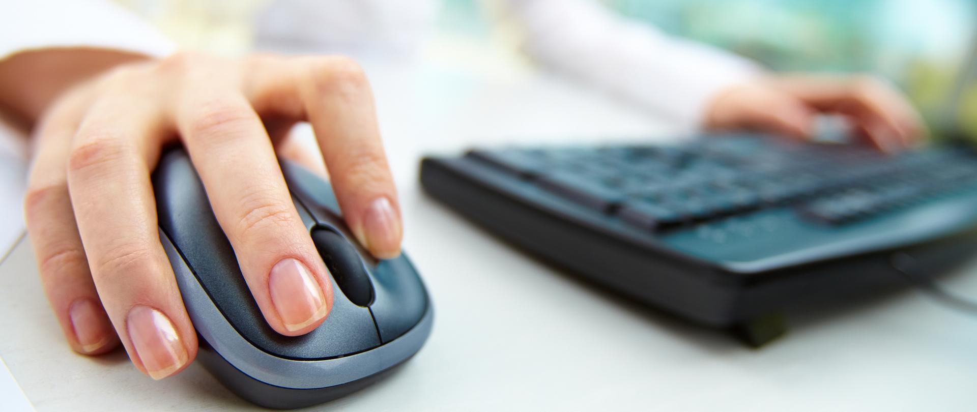 Osoba przed komputerem, jedna ręka na klawiaturze, druga na myszce